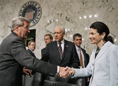 Senate Finance Committee Chairman Sen. Max Baucus, D-Mont., left, shakes hands with committee member Sen. Olympia Snowe, R-Maine, as Sen. Orrin Hatch, R-Utah, is seen at center, Tuesday, Oct. 13, 2009, on Capitol Hill in Washington, after a committee vote regarding the health care reform bill.